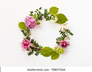 round frame with blooming flowers and leaves on white background. flat lay, top view