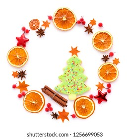 Round frame with dried orange, christmas cookies, anise stars on white background. Flat lay, top view