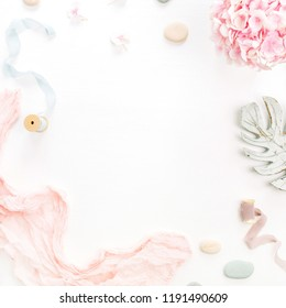 Round frame of hydrangea flower bouquet, eucalyptus branch, pastel pink blanket, monstera leaf plate on white background. Flat lay, top view mockup with space for text.