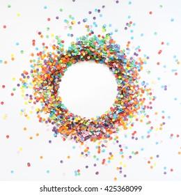 Round frame made of colored confetti. White background. Festive confetti.