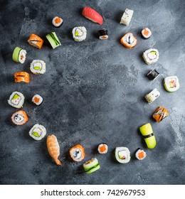 Round frame made of set of Japanese food on dark background. Sushi rolls, nigiri, raw salmon steak, rice and avocado. Flat lay. Top view