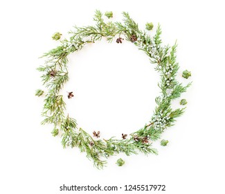Round frame made of winter evergreen plants and natural cones. Christmas flat lay. Top view