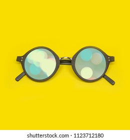 Round frame sunglasses isolated on yellow summer background, blurry festive lights reflected on glass