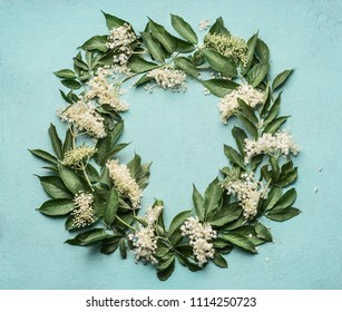 Round frame or wreath of Elderflowers  on blue background, top view