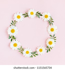 Round frame, wreath made of chamomiles, petals, leaves on beige background. Flat lay, top view