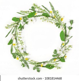 Round frame wreath made of spring flowers and leaves isolated on white background. Flat lay. Top view.
