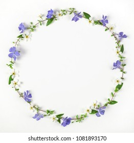 Round frame wreath made of spring wildflowers, lilac flowers and leaves isolated on white background. Top view. Flat lay.