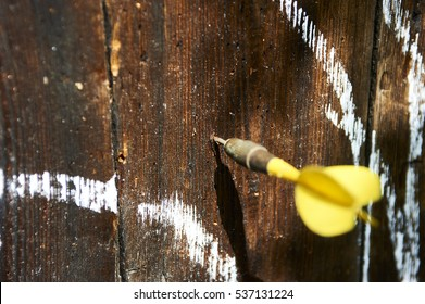 Round of game of darts drawn in chalk on old wooden wall outside. Dart stuck into wood board