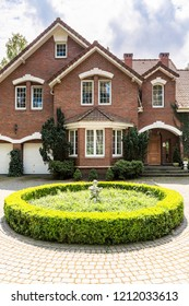 Round garden in front of house in english style with windows and plants