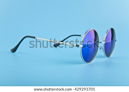 round glasses with dark blue glasses on blue background closeup