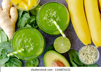 Round glasses filled with green kale and spinach smoothie and green swirled straws surrounded by ingredients