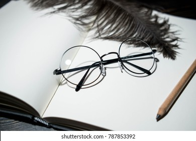round glasses on a book on a wooden background and peacock feather