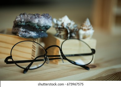 round glasses on a wooden background and cockleshells in wooden box