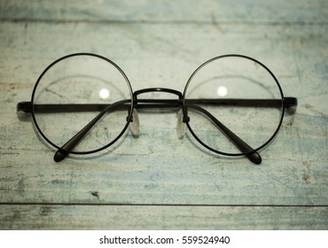 round glasses on a wooden desk
