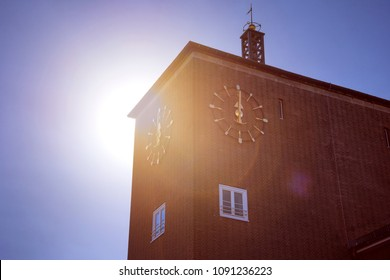 Round golden alarm clock on red brick house against sunlight. The image of the vintage clock shows noon midday 12 twelve - concept timer standard time change alert retro clock design hour signal