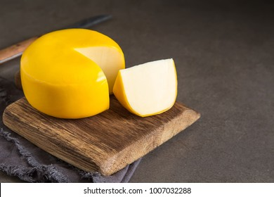 Round gouda cheese. Dark background