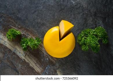 Round gouda cheese with parsley. Dark background