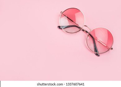 Round gradient sunglasses isolated on pink background.