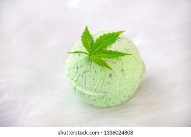 Round green cannabis bath bomb with marijuana leaf isolated on white background