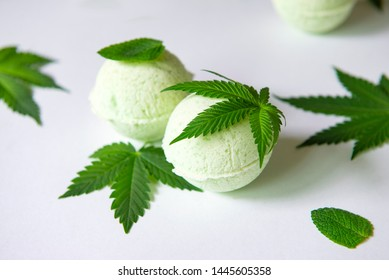 Round green cannabis bath bombs with marijuana leaves isolated on white background