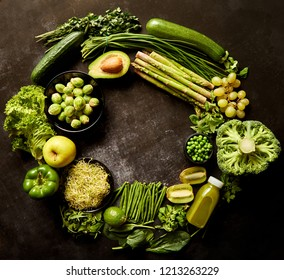 Round green healthy food composition with avocado, broccoli, apple, smoothie, cucomber, asparagus, kiwi, bean. Placed on dark background. Top view with copy space in the middle.