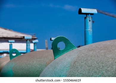 Round green iron tank and a blue pipe on the blue sky. Abstraction scape on the plant. Some details.