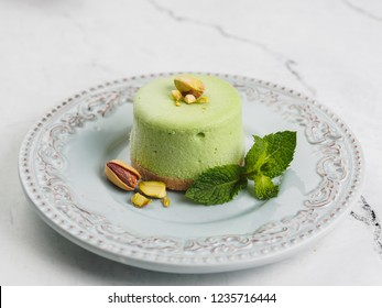 Round green mini cheesecake with pistachio and mint.