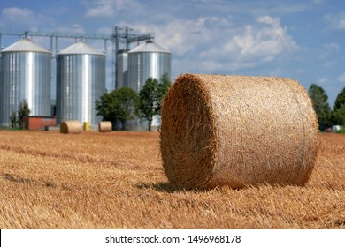 Round Hay Bales on the Field After Harvest Against Grain Silos. Hay Bales and Grain Silos in a Field Against Blue Sky With White Clouds. Beautiful Agricultural Landscape Scenery.
