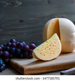 Round head of cheese Kostromskoy with cut piece on wooden background on square plate with grapes. Square with copy space. Traditional product, Kostroma, Russia