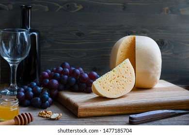 Round head of cheese Kostromskoy with cut piece on wooden background on square plate with grapes, honey, defocused bottle and glass. Horizontal with copy space. Traditional product, Kostroma, Russia