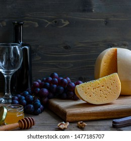 Round head of cheese Kostromskoy with cut piece on wooden background on square plate with grapes, honey, defocused bottle and glass. Square with copy space. Traditional product, Kostroma, Russia