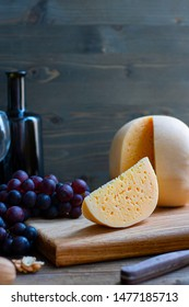 Round head of cheese Kostromskoy with cut piece on wooden background on square plate with grapes, honey, defocused bottle and glass. Vertical with copy space. Traditional product, Kostroma, Russia