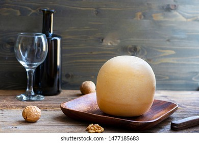 Round head of cheese Kostromskoy on textured dark wooden background on the square plate with walnuts and defocused bottle and glass. Horizontal with copy space. Traditional product, Kostroma, Russia