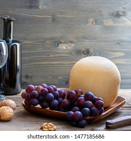 Round head of cheese Kostromskoy on textured dark wooden background on the square plate with grapes and defocused bottle and glass. Square with copy space. Traditional product, Kostroma, Russia