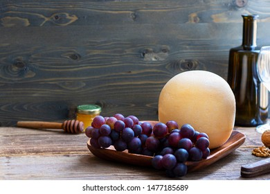 Round head of cheese Kostromskoy on textured dark wooden background on square plate with grapes, honey, defocused bottle and glass. Horizontal with copy space. Traditional product, Kostroma, Russia
