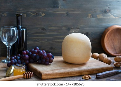 Round head of cheese Kostromskoy on textured dark wooden background on square plate with grapes, honey, walnuts, defocused bottle and glass. Horizontal copy space Traditional product, Kostroma, Russia
