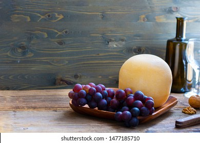 Round head of cheese Kostromskoy on textured dark wooden background on the square plate with grapes and defocused bottle and glass. Horizontal with copy space. Traditional product, Kostroma, Russia