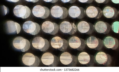 Round hole multilayered glass background. Fuzzy backdrop. Grunge texture of dirty glass surface closeup through circled lattice window. Abstract background with layers of blurred light dots.