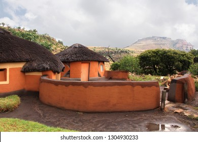 Round huts or rondavels surrounded by clay fence in the village of Basotho tribe. Drakensberg mountains background. South Africa. Ethnic buildings with the straw roof. African traditional houses.