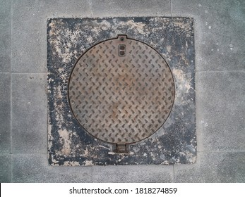 Round iron looks of the old manhole on the floor. (Manhole cover)