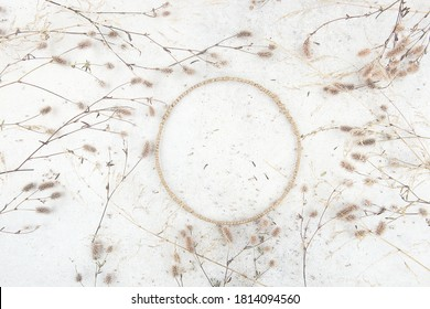 Round jute frame with dried grasses on stone tile background. Composition of dried flowers and  circle frame indoor.