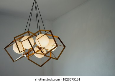 A round lamp with a rectangular iron frame suspended from the ceiling, illuminating in gold. Interior concept.