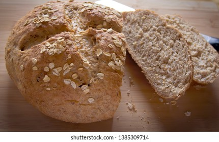 A round loaf of artisan whole-grain bread with scored crust, garnished with rolled oats, overhead shot, resting on a bamboo cutting board next to a bread knife.