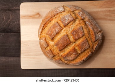 Round loaf bread on black wooden table