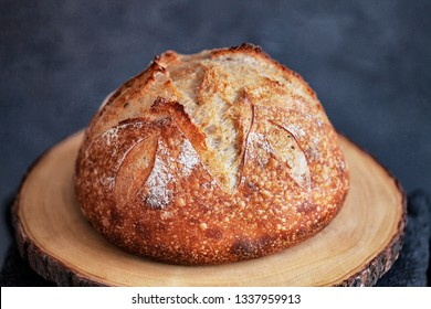 Round loaf of freshly baked homemade artisan sourdough bread on a round wood plank