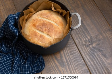 Round Loaf of Freshly Baked Sourdough Bread in Parchment-Lined Dutch Oven on Wood Table