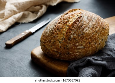 Round loaf of freshly baked sourdough bread with knife on cutting board. Artisan bread with seeds on dark table. Rustic sourdough bread.