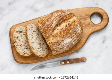 Round loaf of freshly baked sourdough bread with knife on cutting board, top view. Artisan bread with seeds on marble table. Rustic sourdough bread.