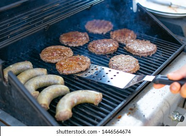 round meat patties and sausages are cooked on the grill. space for text
