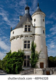 A round medieval tower with pointed turrets from Normandy, France.  The tower is white brick and stucco and has green ivy growing on the sides.  Beautiful blue sky with white clouds in the background.